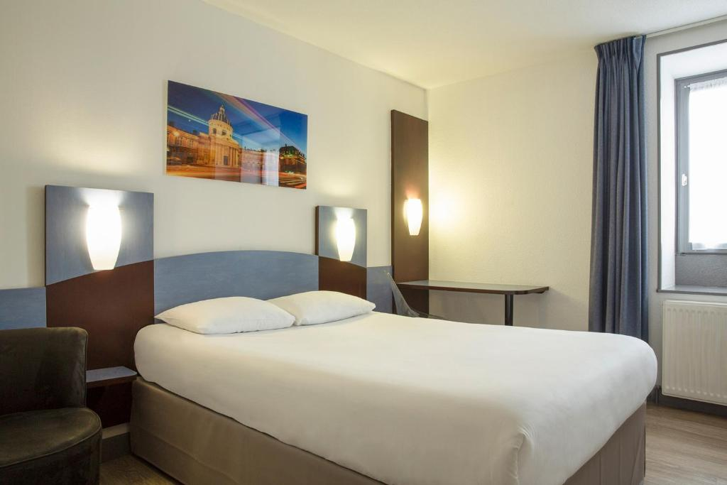 A bed or beds in a room at The Originals Access, Hôtel Bourges Gare