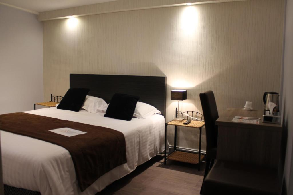 A bed or beds in a room at Hôtel L'Univers