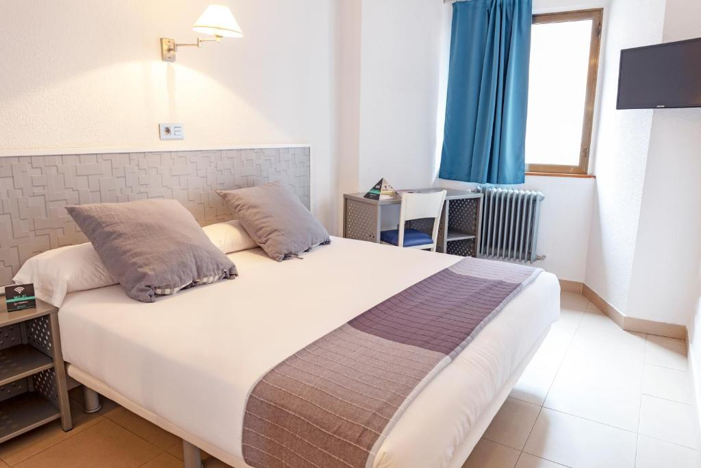 A bed or beds in a room at Hotel Alda Centro Palencia