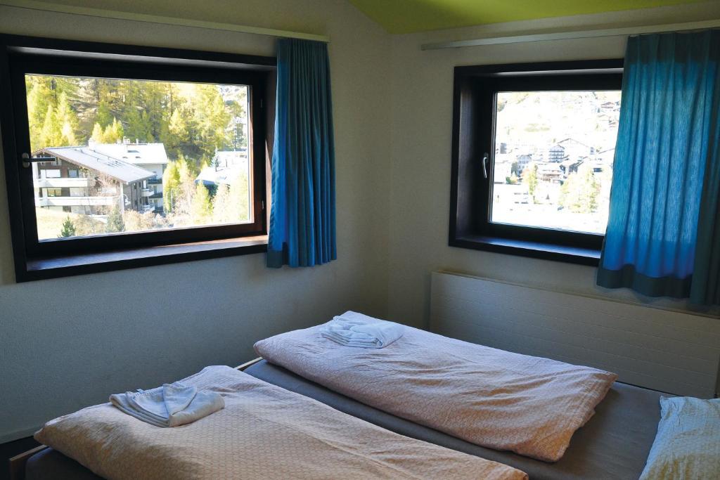 Een bed of bedden in een kamer bij Zermatt Youth Hostel - Private Rooms