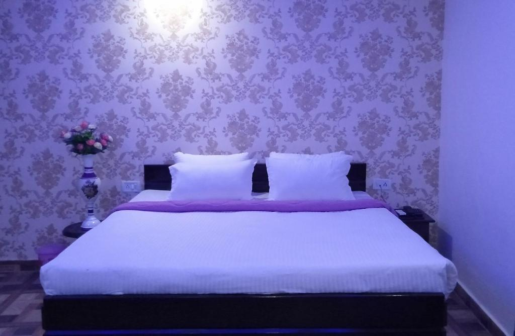 A bed or beds in a room at RAJSHREE INN