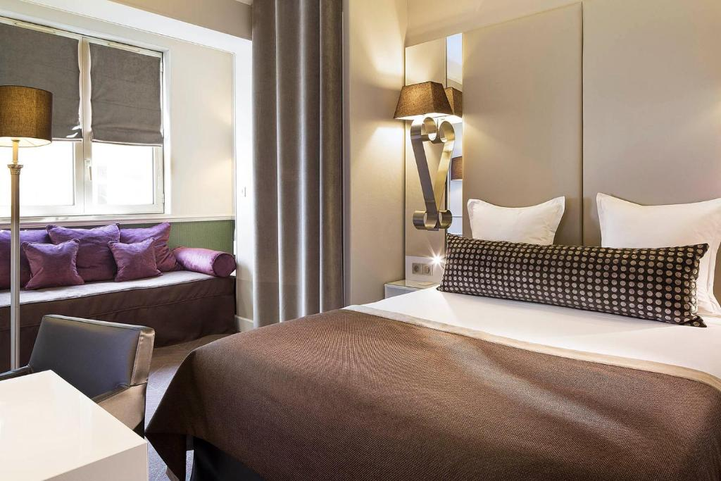 A bed or beds in a room at Hôtel Galileo Champs Elysées