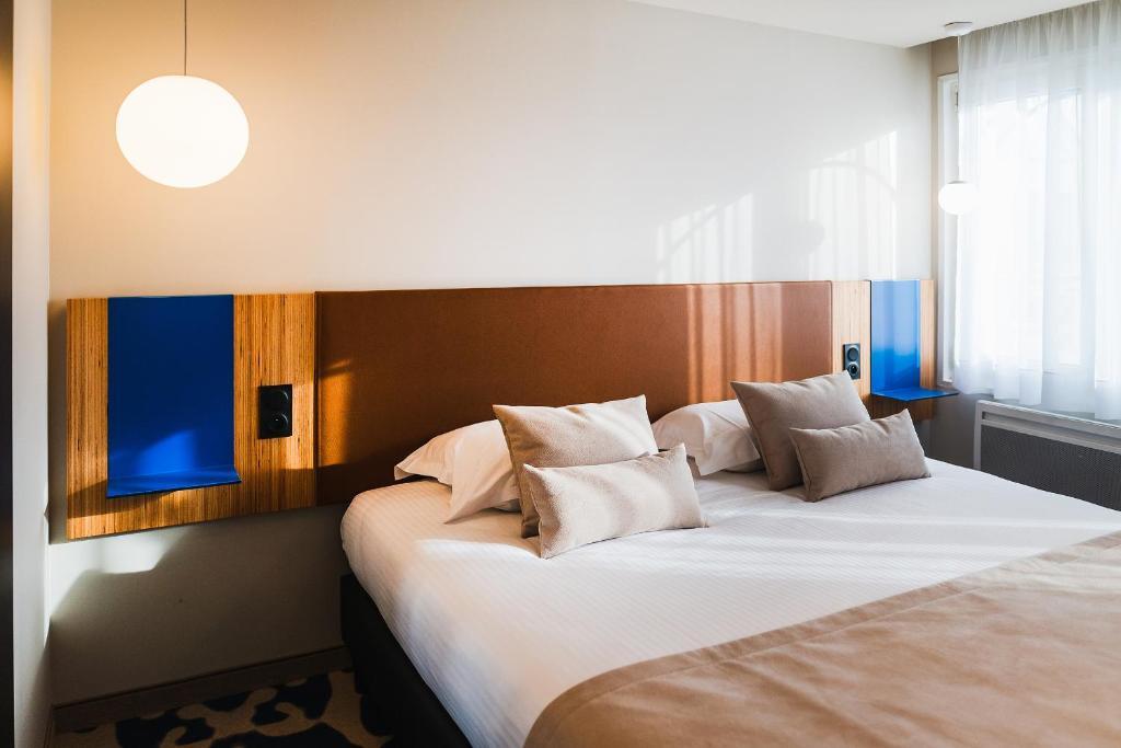 Un ou plusieurs lits dans un hébergement de l'établissement Hotel Le Bugatti