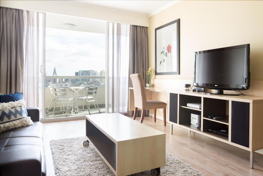 A television and/or entertainment center at Resort Living And Darling Harbour At Your Door