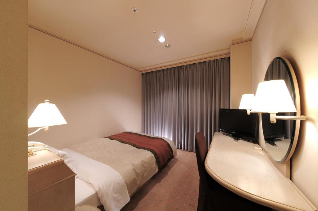 A bed or beds in a room at Takarazuka Washington Hotel