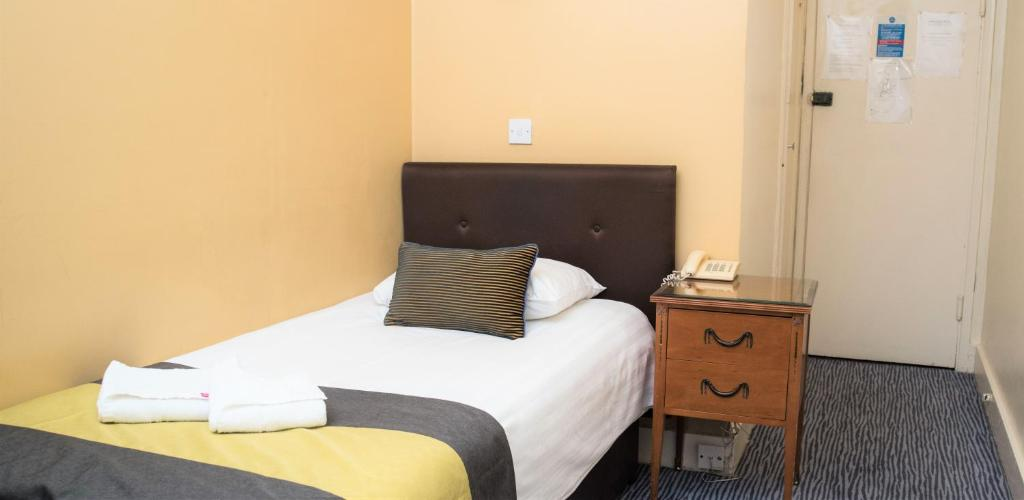 A bed or beds in a room at Rose Court Hotel