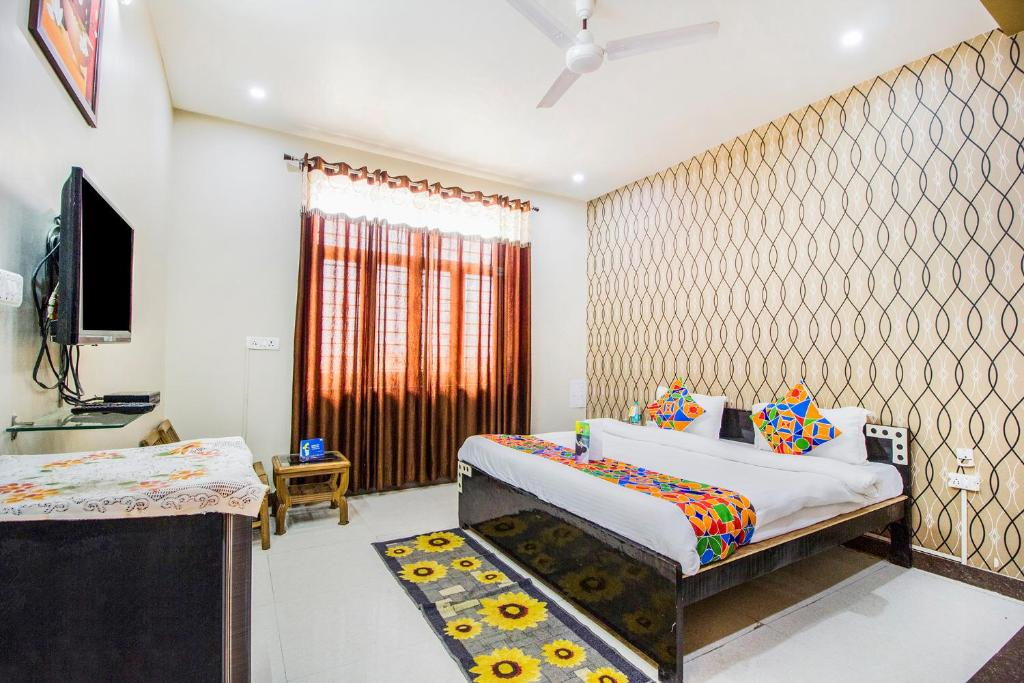 A bed or beds in a room at FabHotel Queen Palace