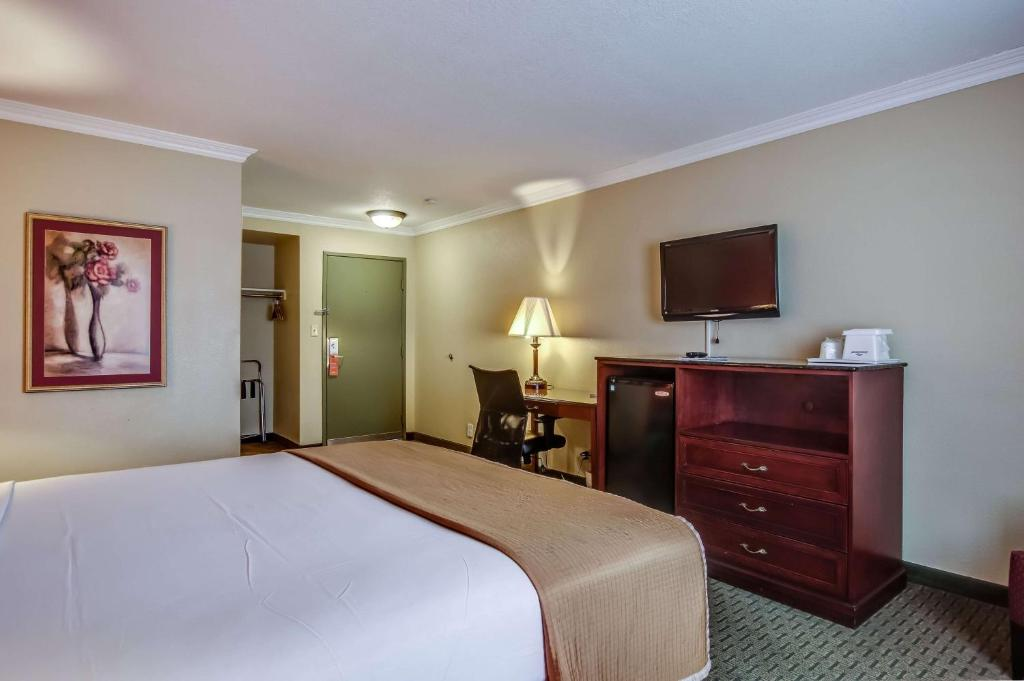 A bed or beds in a room at Howard Johnson by Wyndham Reseda Hotel & Suites