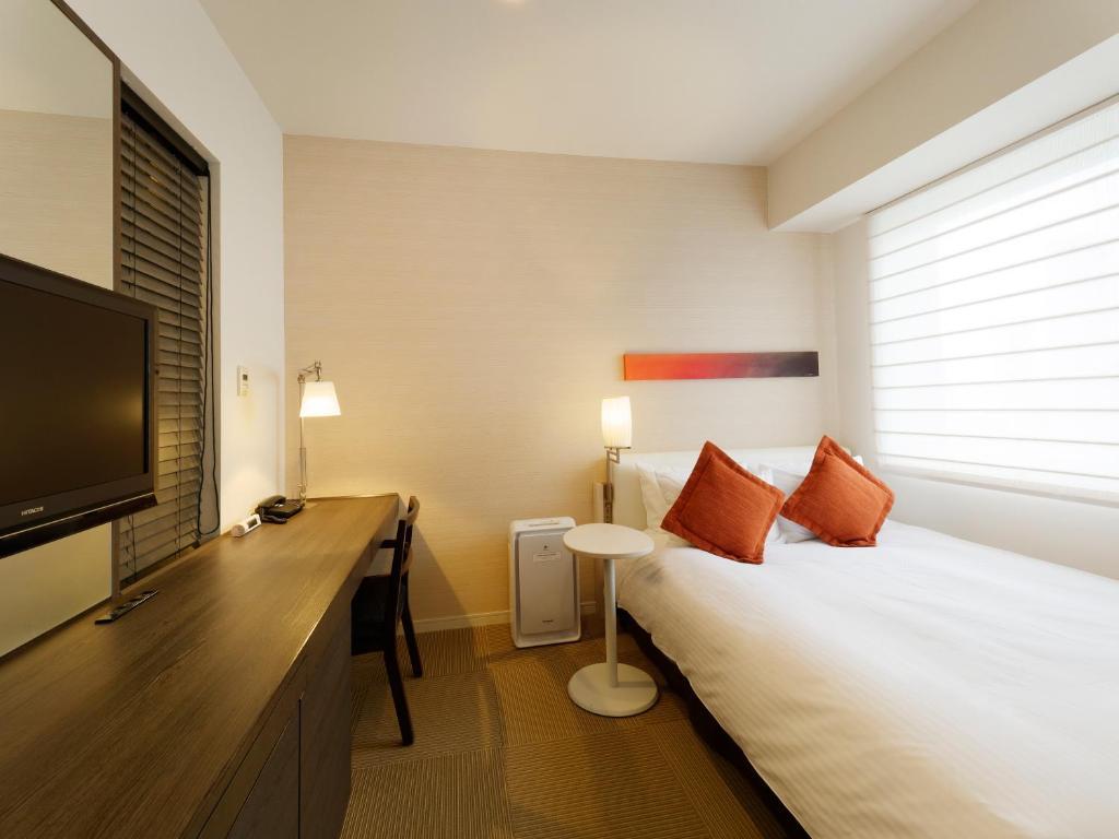 A bed or beds in a room at Hotel Keihan Tokyo Yotsuya