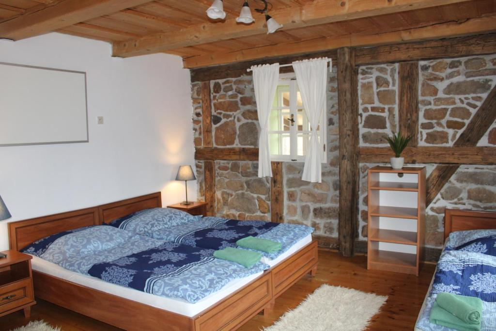 A bed or beds in a room at Penzion Modrý Svět