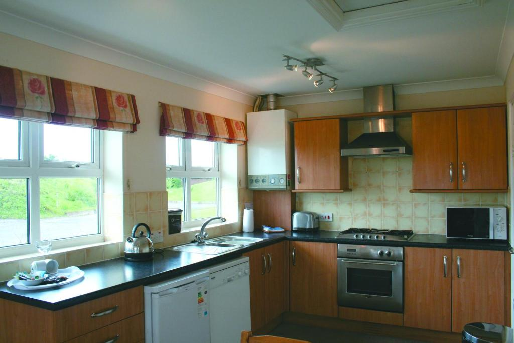 A kitchen or kitchenette at The Snug - Lakeside bungalow with 2 bedrooms