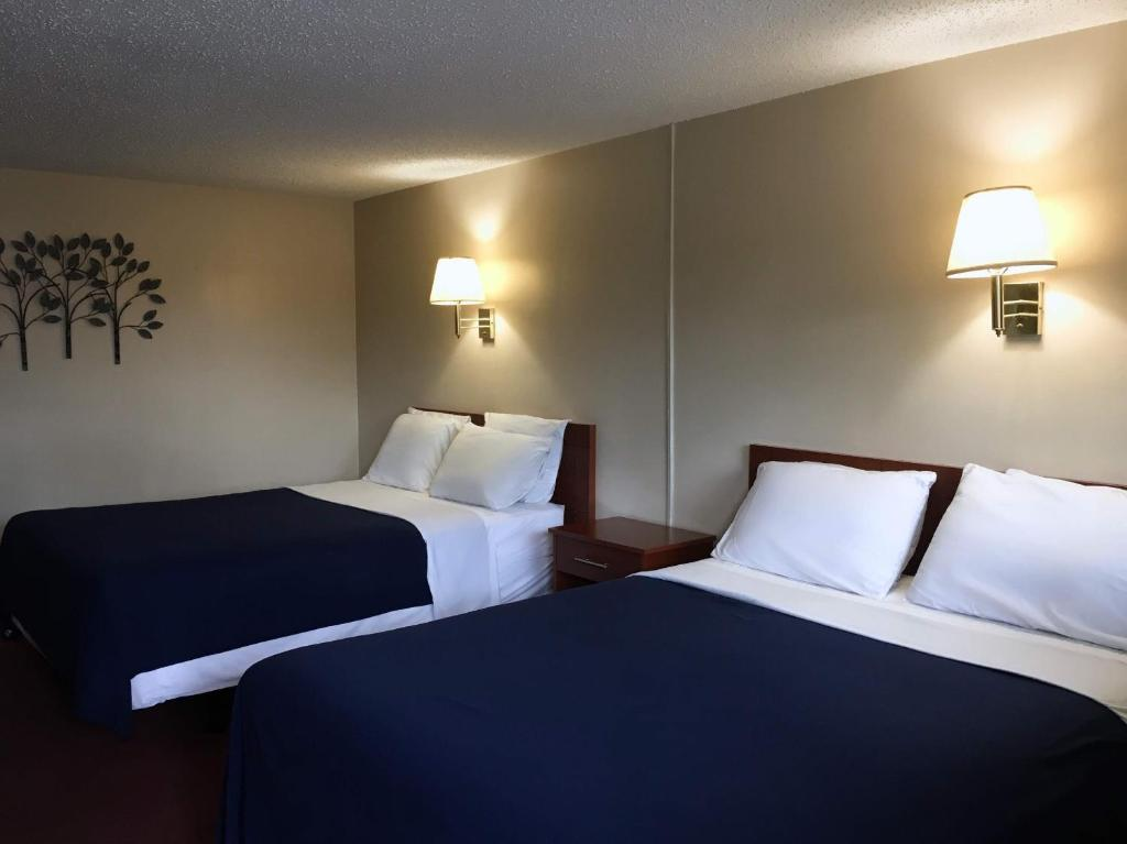 A bed or beds in a room at Swiss Cottage Inn