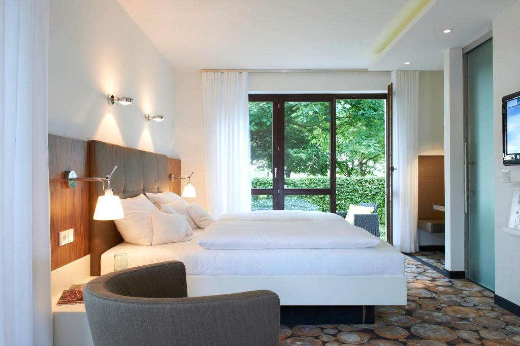 A bed or beds in a room at Mintrops Land Hotel Burgaltendorf
