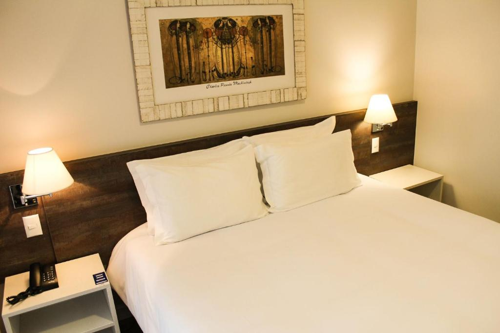 A bed or beds in a room at Charrua Hotel