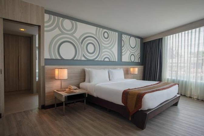 A bed or beds in a room at Nora Chaweng Hotel