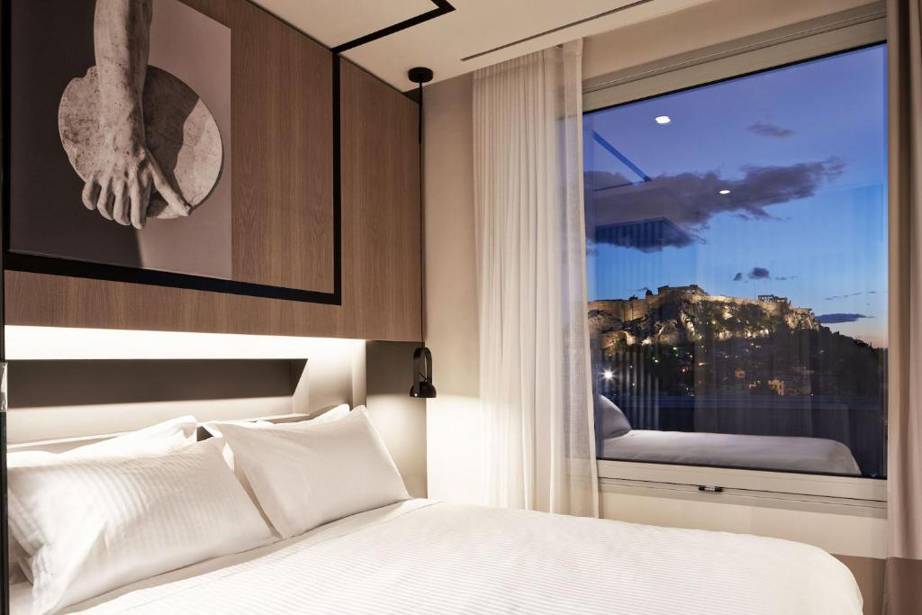 A bed or beds in a room at Urban Frame Hotel