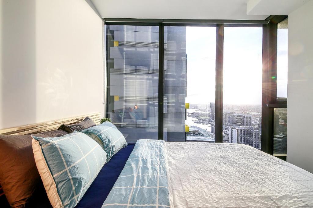 A bed or beds in a room at A Cozy Suite with a View of Docklands & The Yarra