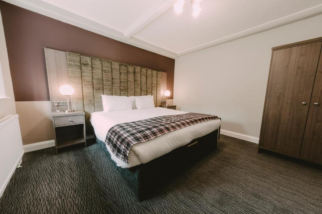 A bed or beds in a room at Ramada Resort Cwrt Bleddyn Hotel & Spa