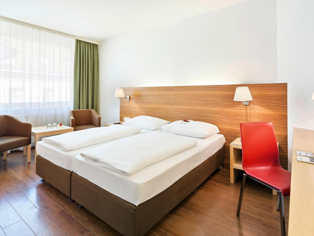 A bed or beds in a room at Austria Trend Hotel beim Theresianum Wien