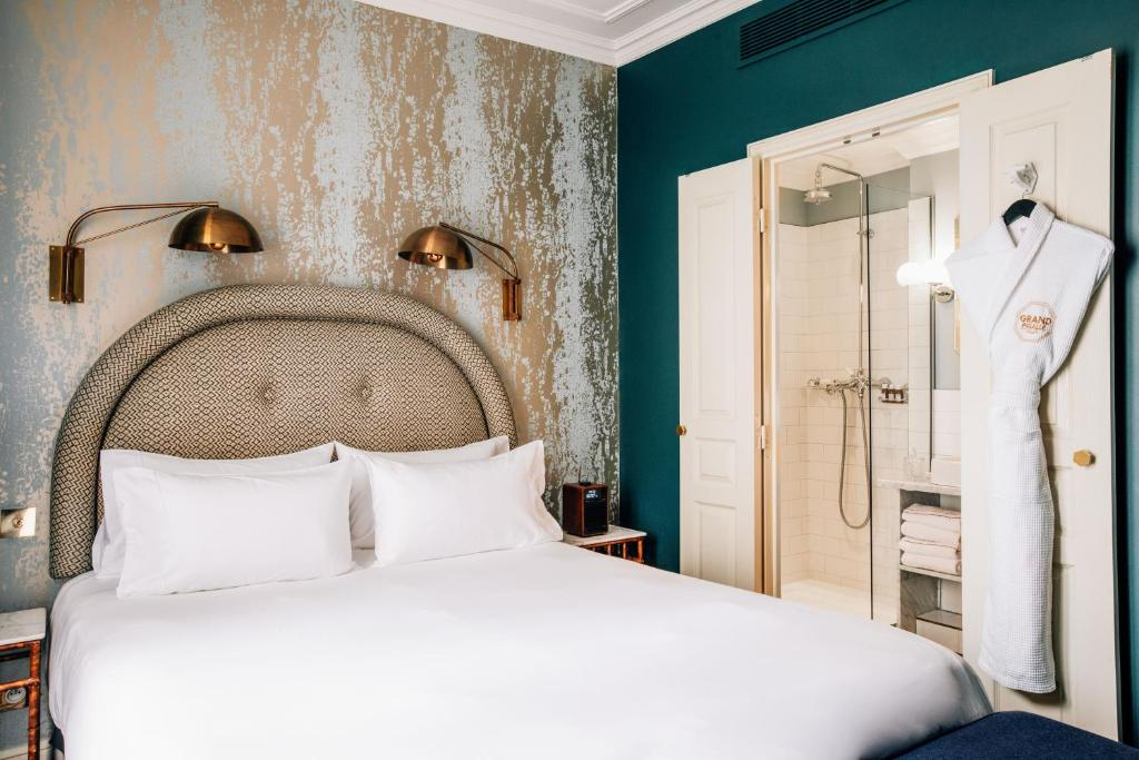 A bed or beds in a room at Grand Pigalle Hotel
