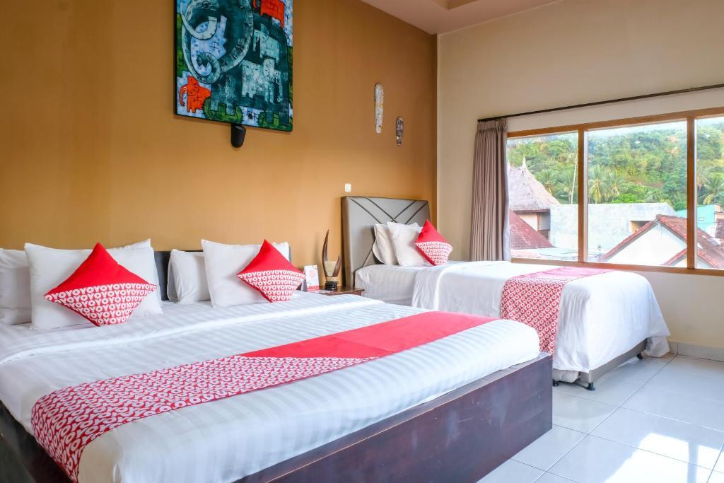 A bed or beds in a room at OYO 992 Semilir Senggigi Inn
