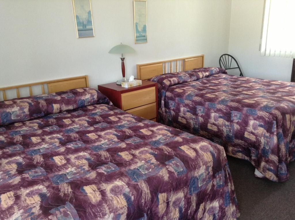 A bed or beds in a room at Motel St-Thomas