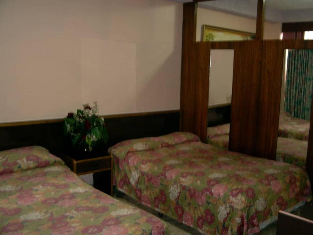 A bed or beds in a room at Hotel Gran Galaxie