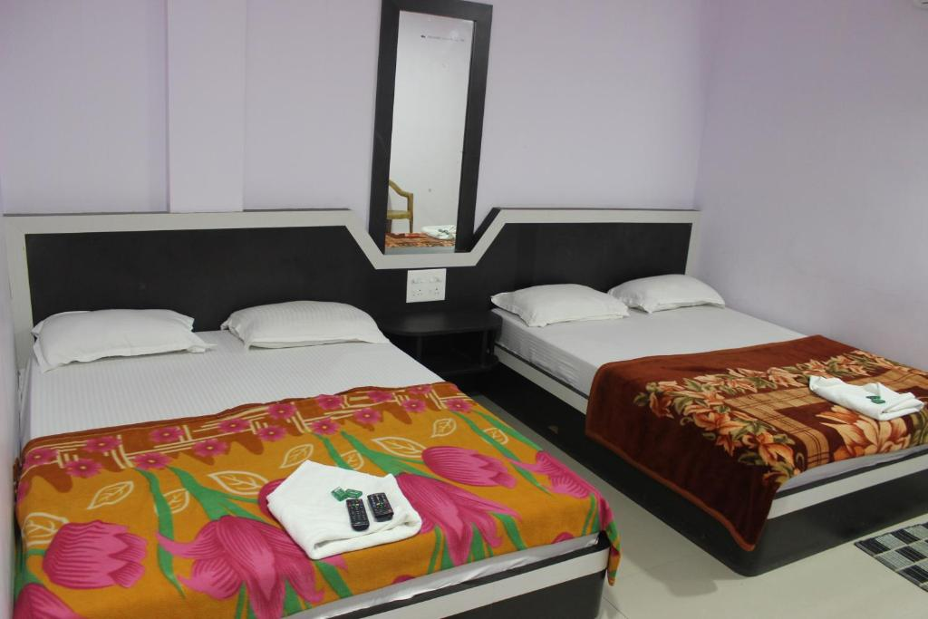 A bed or beds in a room at Hotel Amullya