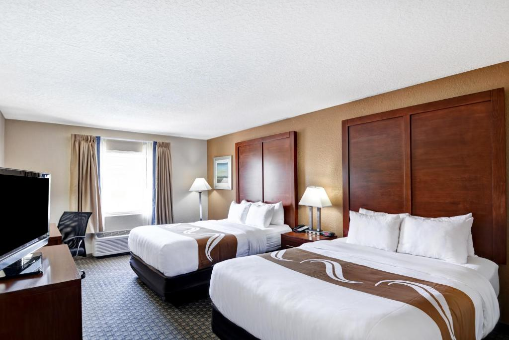 A bed or beds in a room at Quality Inn & Suites Heritage Park