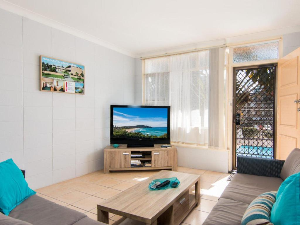 A television and/or entertainment center at Forster Holiday Lodge 19