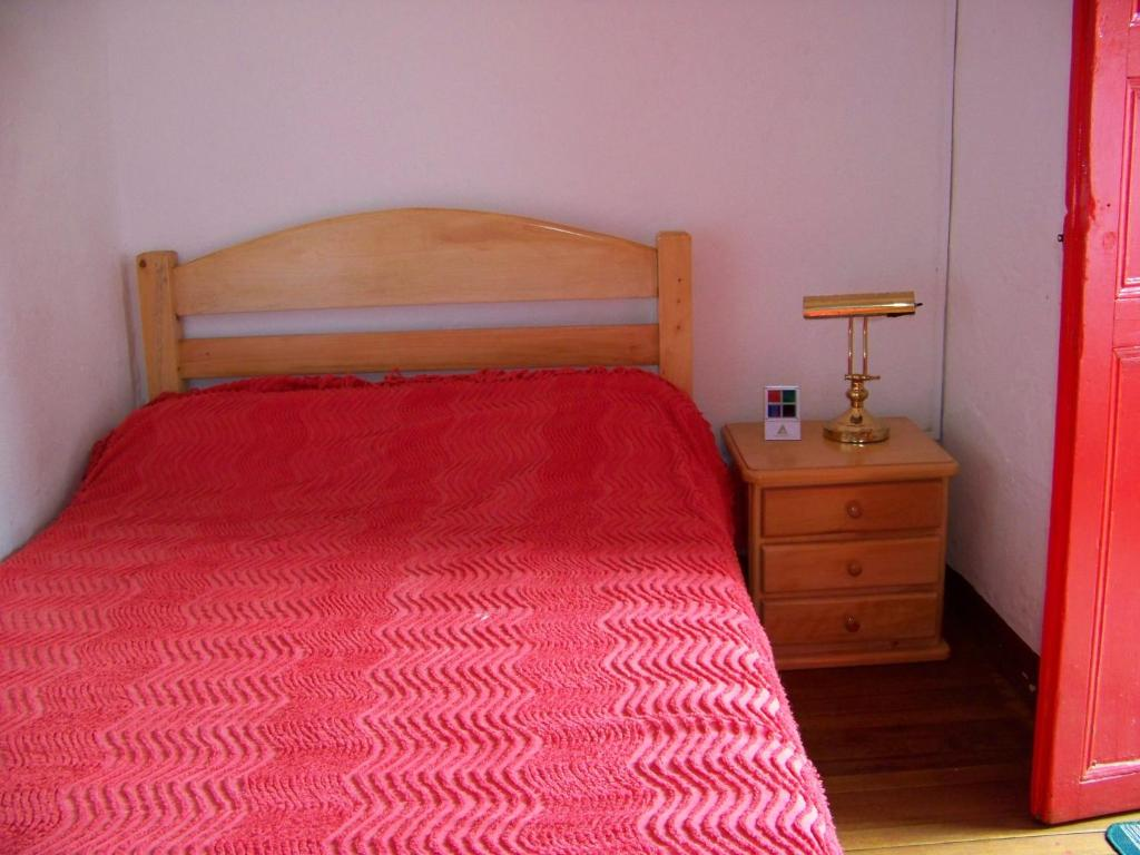 A bed or beds in a room at Hostal Baluarte De La Candelaria