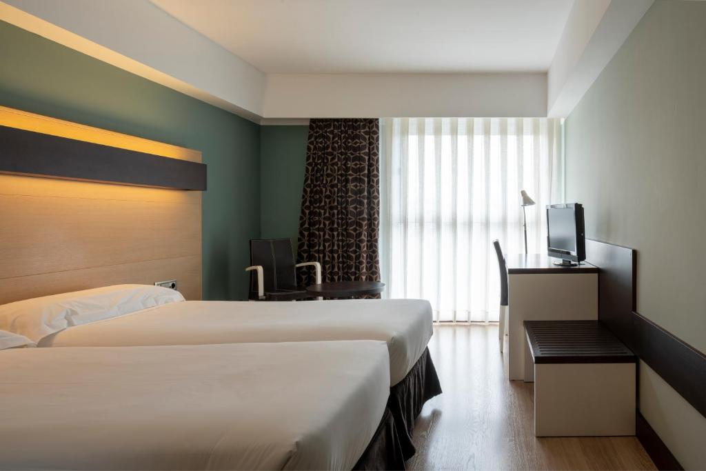 A bed or beds in a room at Hotel Ciudad de Logroño
