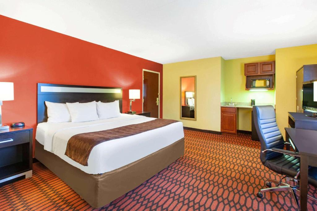 A bed or beds in a room at Baymont by Wyndham Harrisburg