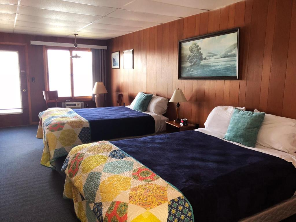 A bed or beds in a room at Showboat Motel Restaurant & Bar
