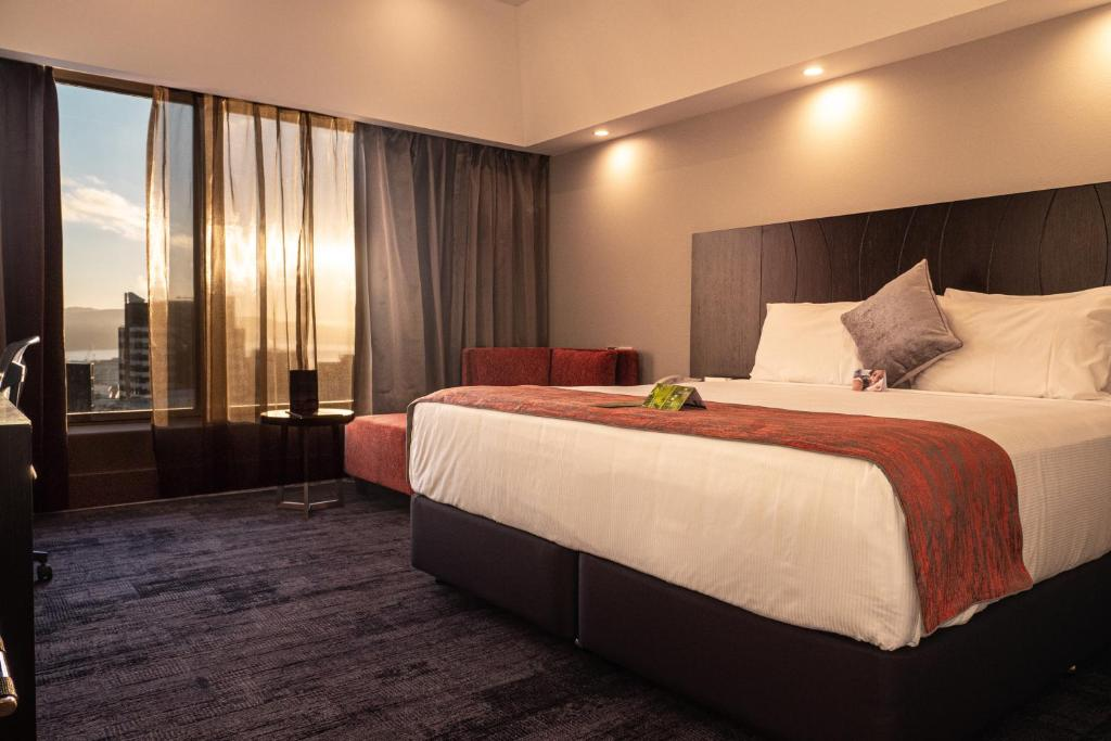 A bed or beds in a room at James Cook Hotel Grand Chancellor