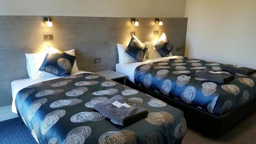 A bed or beds in a room at Colac Central Hotel-Motel