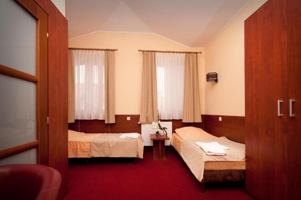 A bed or beds in a room at Hotelik Amber
