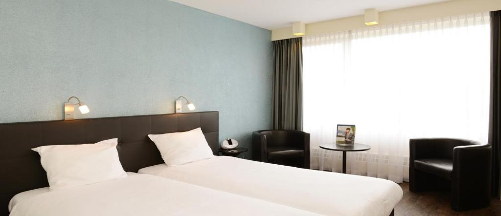 A bed or beds in a room at Amrâth Hotel Brabant