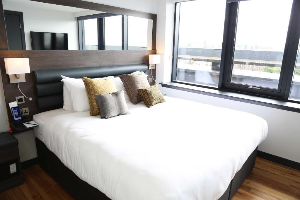 A bed or beds in a room at Haymarket Hub Hotel