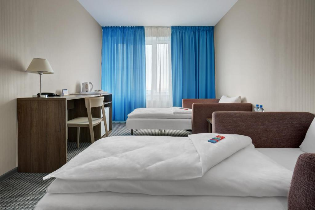 A bed or beds in a room at Zvezdnaya Hotel