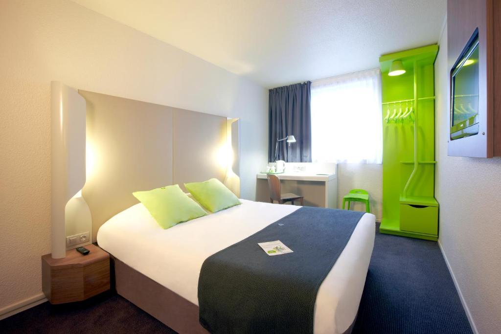 Een bed of bedden in een kamer bij Campanile Paris 19 - La Villette
