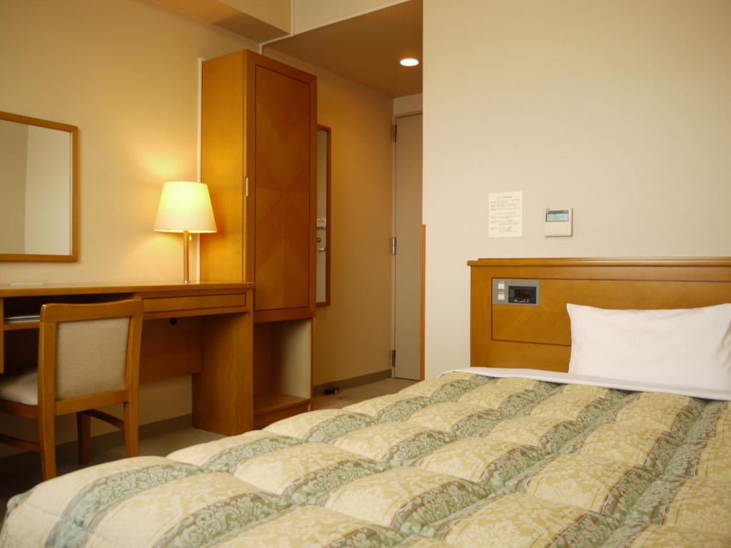 A bed or beds in a room at Hotel Route-Inn Jouetsu
