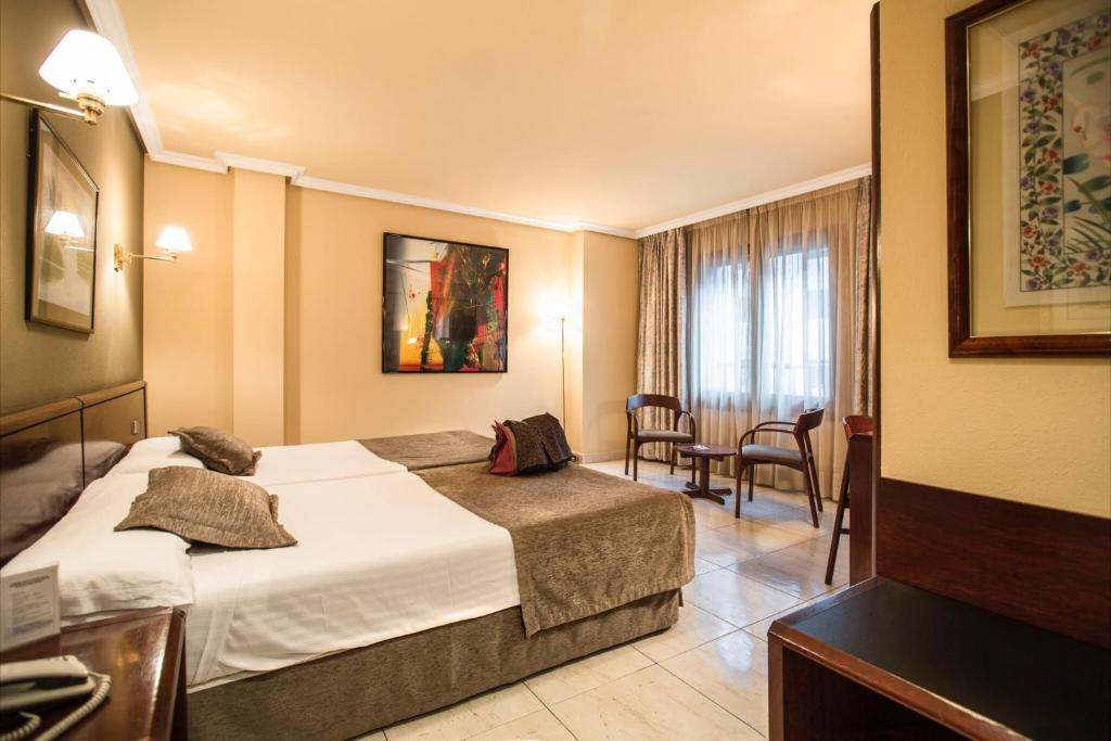 A bed or beds in a room at Imperial Atiram Hotel