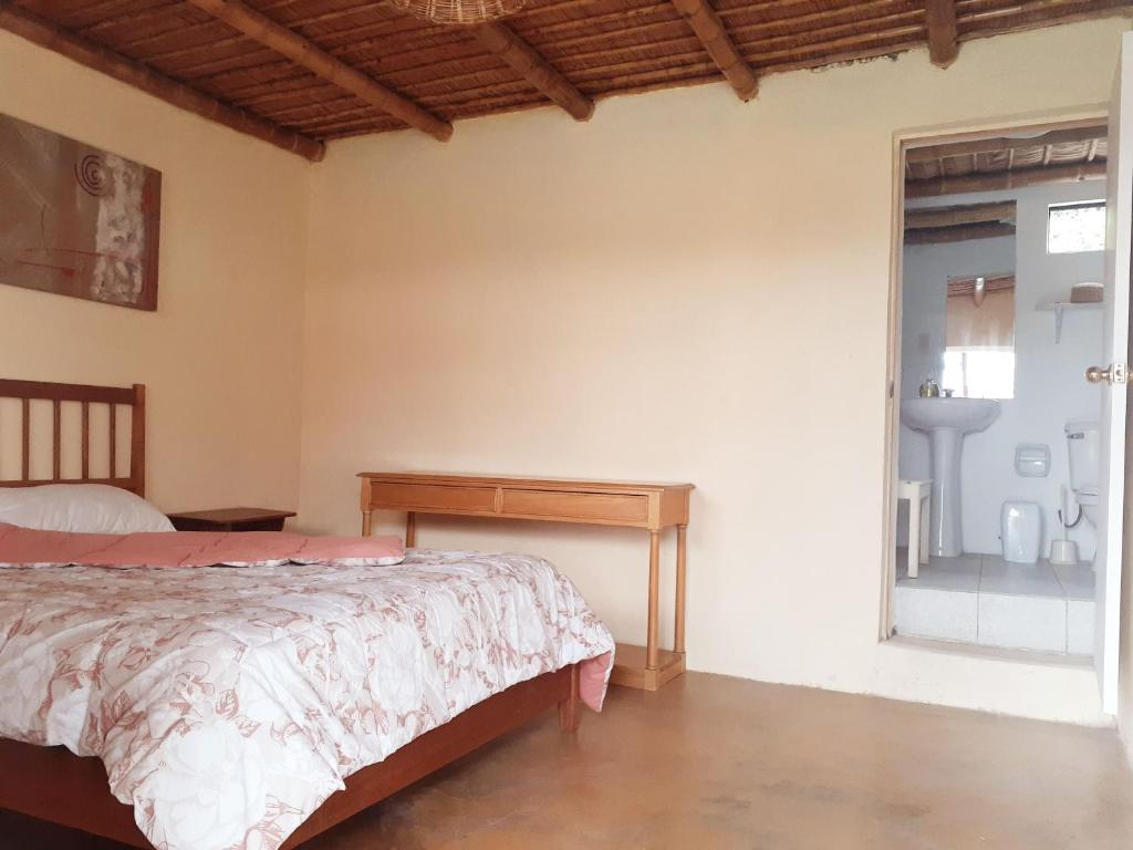A bed or beds in a room at CHINCHA'S COUNTRY LODGE