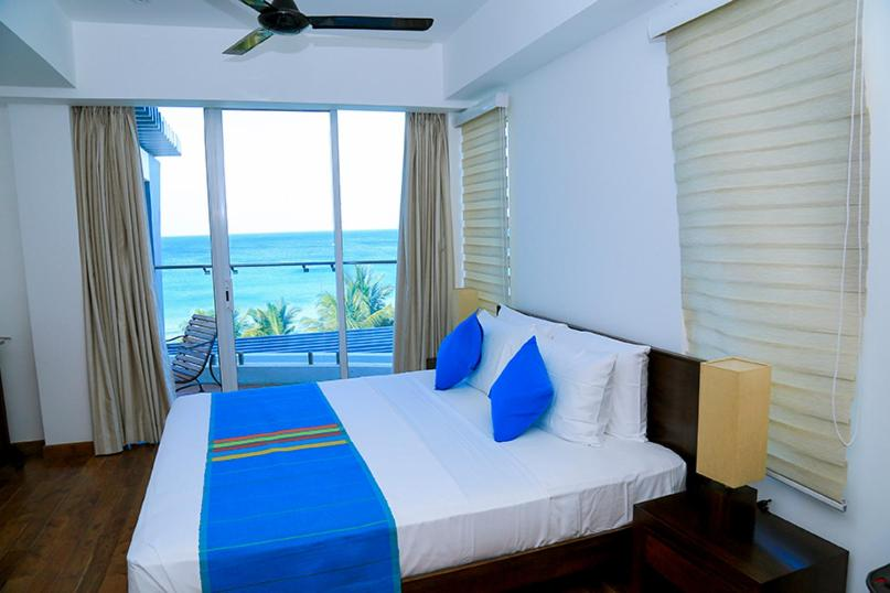 A bed or beds in a room at Nilaveli Beachfront Penthouse by Oceanfront Condominiums