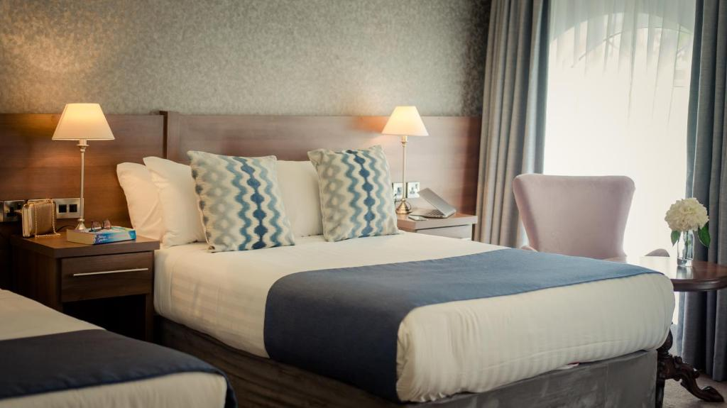 A bed or beds in a room at Woodford Dolmen Hotel Carlow