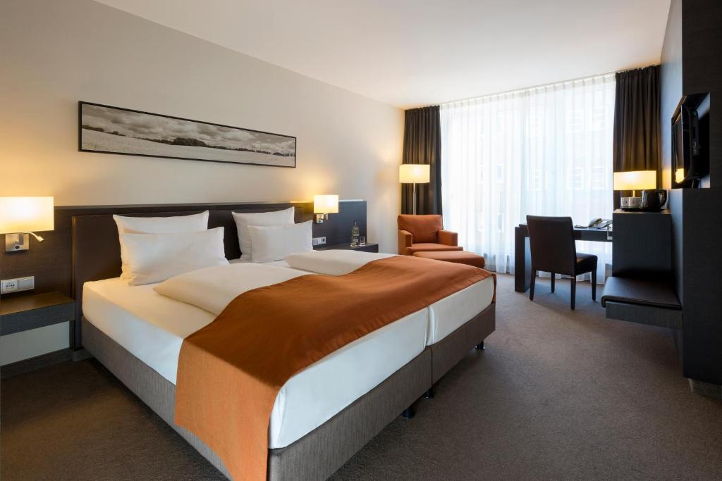 A bed or beds in a room at Atlantic Hotel Lübeck