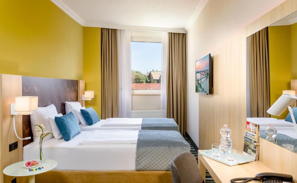 Ένα ή περισσότερα κρεβάτια σε δωμάτιο στο Leonardo Hotel Budapest