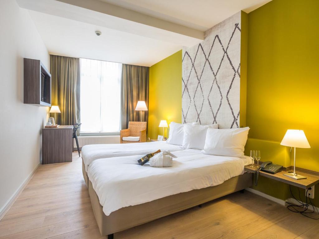 Een bed of bedden in een kamer bij Hotel Au Quartier