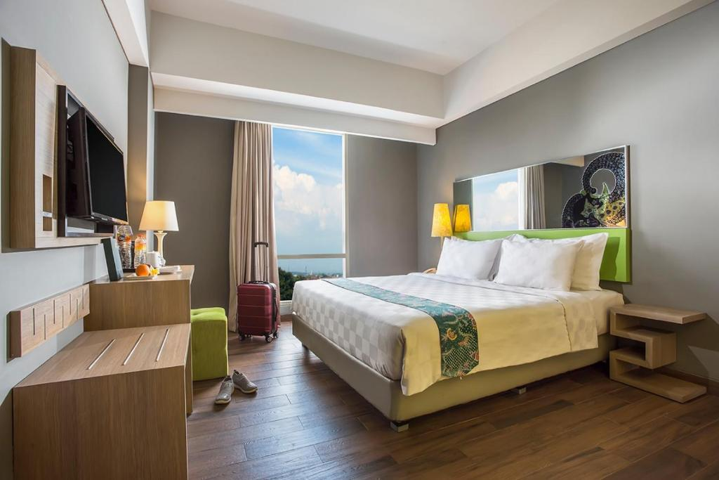 A bed or beds in a room at Pesonna Hotel Semarang